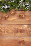 Christmas fir tree with snow and baubles on rustic wooden board Royalty Free Stock Image