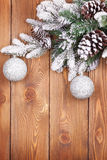 Christmas fir tree with snow and baubles on rustic wooden board Royalty Free Stock Photo