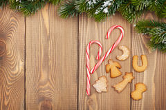 Christmas fir tree with snow, candy cane and gingerbread cookies. On rustic wooden board with copy space Royalty Free Stock Photography