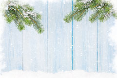 Christmas fir tree in snow in front of wooden wall Stock Image
