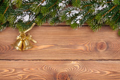 Christmas fir tree with snow and holiday decor on rustic wooden. Board with paper for copy space Royalty Free Stock Photos