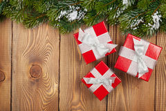 Christmas fir tree with snow and red gift boxes Stock Images