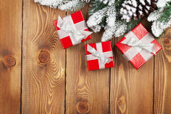 Christmas fir tree with snow and red gift boxes Royalty Free Stock Photos