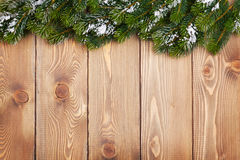 Christmas fir tree with snow on rustic wooden board. With copy space Stock Photo
