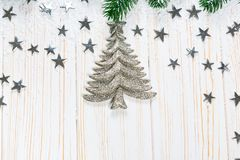 Christmas fir tree in snow with silver stars on white wooden background. Christmas fir tree in snow with silver stars and New Year decor toy on white wooden Stock Photos