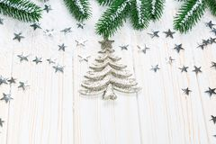 Christmas fir tree in snow with silver stars on white wooden background. Christmas fir tree in snow with silver stars and New Year decor toy on white wooden Royalty Free Stock Photo