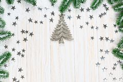 Christmas fir tree in snow with silver stars on white wooden background. Christmas fir tree in snow with silver stars and New Year decor toy on white wooden Royalty Free Stock Images
