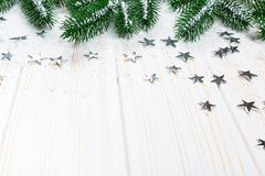 Christmas fir tree in snow with silver stars on white wooden background. Free space. Winter frame Stock Photography