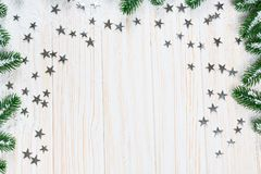 Christmas fir tree in snow with silver stars on white wooden background. Free space. Winter frame Royalty Free Stock Images