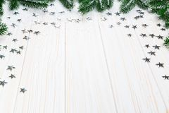 Christmas fir tree in snow with silver stars on white wooden background. Free space. Winter frame Royalty Free Stock Photography
