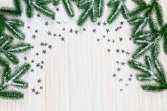 Christmas fir tree in snow with silver stars on white wooden background. Free space. Winter frame Stock Photo