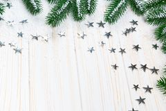 Christmas fir tree in snow with silver stars on white wooden background. Free space. Winter frame Royalty Free Stock Image