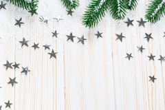 Christmas fir tree in snow with silver stars on white wooden background. Free space. Winter frame Royalty Free Stock Photo
