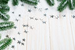 Christmas fir tree in snow with silver stars on white wooden background. Free space. Winter frame Royalty Free Stock Photos