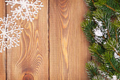 Christmas fir tree with snow and snowflake decor on rustic woode Stock Images