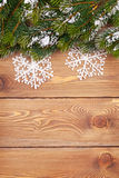 Christmas fir tree with snow and snowflake decor on rustic woode Stock Image