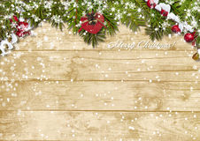 Christmas fir tree with snowfall on a wooden board. Christmas  wooden background  with  beautiful Christmas garland and snow Royalty Free Stock Photography