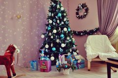 Christmas fir tree with toys. Beautiful Christmas tree with toys, gifts and various ornaments in the apartment Stock Images