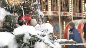 Christmas fir tree with toys close-up. Decoration of the city for the holiday. In the background out of focus turns the. Carousel, on which the children ride stock video