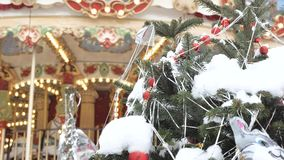 Christmas fir tree with toys close-up. Decoration of the city for the holiday. In the background out of focus turns the. Carousel, on which the children ride stock footage