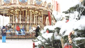 Christmas fir tree with toys close-up. Decoration of the city for the holiday. In the background out of focus turns the. Carousel, on which the children ride stock video footage