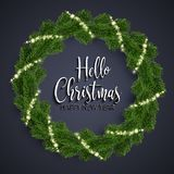 Christmas fir-tree wreath and glowing sparks. Hello Christmas and Happy New Year lettering . Christmas fir-tree wreath and holly glowing lights on black Royalty Free Stock Photography