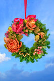 Christmas fir tree wreath hanged over blue sky. Christmas fir tree wreath decorated with fruits and flowers hanged over blue sky Stock Photos