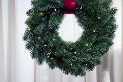 Christmas fir-tree wreath illuminated by garland on white wall royalty free stock photos