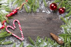 Christmas fir trees in snow with cone, red ribbon, christmas red balls and candy canes on a dark wooden board. Copy space for your Stock Photography
