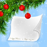 Christmas fir twigs and red balls with white paper scroll. On a blue background Royalty Free Stock Images