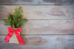 Christmas Firbranch with cones, red polka dot ribbon in the rustic bag on old wooden background stock image