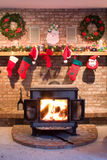 Christmas Fireplace. Christmas house festive inside view. Burning roaring fire in a wood burning stove surrounded by brick and a wood mantle with hanging Royalty Free Stock Images