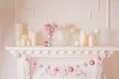 Christmas Fireplace, Hanging pink ornaments, christmas decor Toys on Fire Place, Xmas Magic Story in Lighting Interior royalty free stock photos