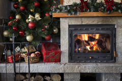 Christmas fireplace and tree decorated with baubles Stock Photo
