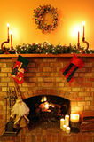 Christmas Fireside. Open log fire, with Christmas candles, garland, broomstick Santa, and stockings Royalty Free Stock Photography