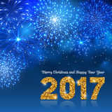 Christmas Fireworks. Christmas festive firework bursting in various shapes and blue colors sparkling against night background. Lettering 2017 with golden glitter Stock Photo