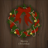 Christmas firry wreath with red ribbon, bow, beads, bolls and bu. Vector christmas firry wreath with red ribbon, bow, beads, bolls and bumps. Wood background Royalty Free Stock Images
