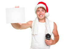 Christmas fitness man showing gift card. Christmas santa exercise man showing white gift / business card for holiday message. Fit young man wearing santa hat Royalty Free Stock Photography