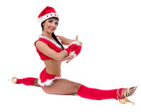 Christmas fitness woman doing the splits wearing santa, isolated on white background. Royalty Free Stock Image