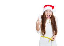 Christmas fitness woman excited about weight loss measuring waist with tape wearing santa hat screaming excited showing thumb up Stock Photo