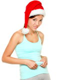 Christmas fitness woman - funny weight loss. Concept of fit young woman showing her belly fat after Christmas. Young female asian caucasian model isolated on Stock Images