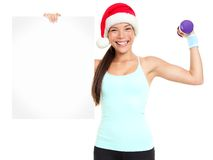Christmas fitness woman showing sign. Standing with red santa hat  on white background. Fit smiling happy fitness model of mixed Asian Chinese and Caucasian Royalty Free Stock Photography