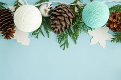 Christmas flat lay composition with fir branches, pine cones, decorations and Christmas lights on the blue background. Christmas flat lay composition with fir Royalty Free Stock Photo