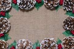 Christmas flat-lay frame of pinecones, holly leaves, and red berries on rustic fabric background royalty free stock photos