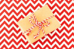 Christmas flat-lay of hand crafted gift box of kraft wrapping paper on red with white textile tablecloth. Copy space stock images