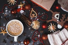 Christmas flat lay of hot coffee or cocoa on a black wooden background with handmade Christmas toys, red balls, beads, cloves and stock photography