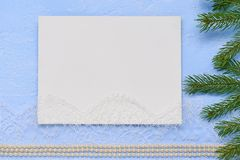 Christmas flat lay Primed cardboard for painting on the backgrou. Nd of decorative plaster, fir branches and beads Stock Photos
