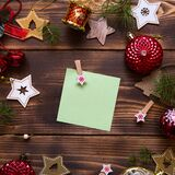 Christmas flat lay of red balloons and wooden stars and clothespins on a dark background with a square sheet for notes in the cent