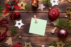 Christmas flat lay of red balloons and wooden stars and clothespins on a dark background with a square sheet for notes in the