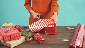 Woman wrapping gift box with decorating items on wood table, close up, top view. stock video